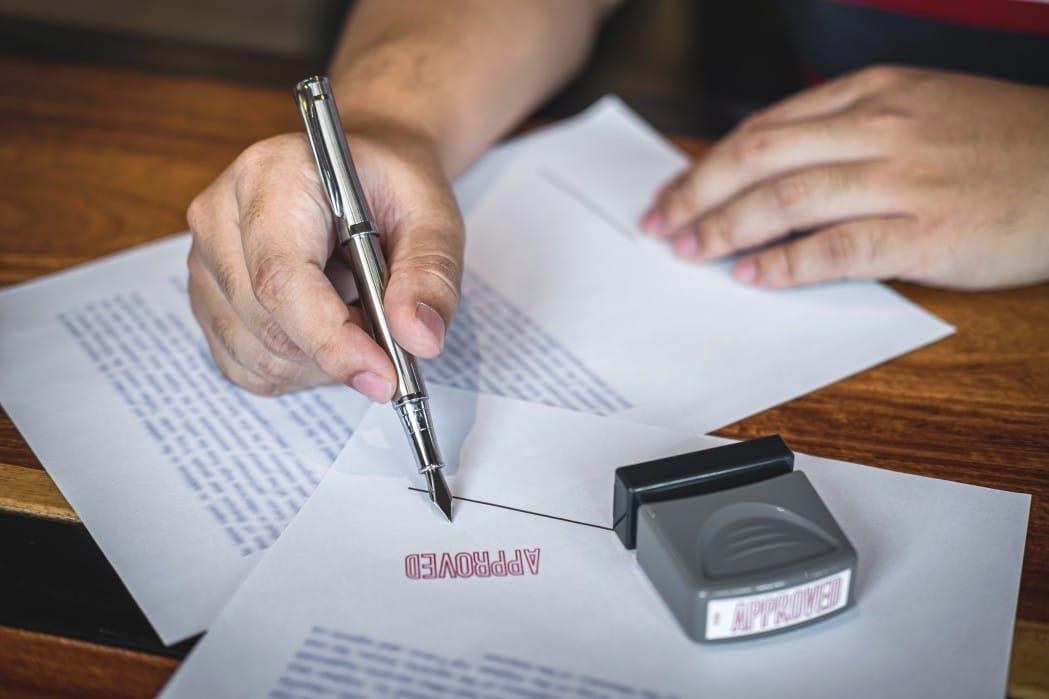 Retificação de Registro Civil - pessoa segurando uma caneta, apoiada em um documento carimbado