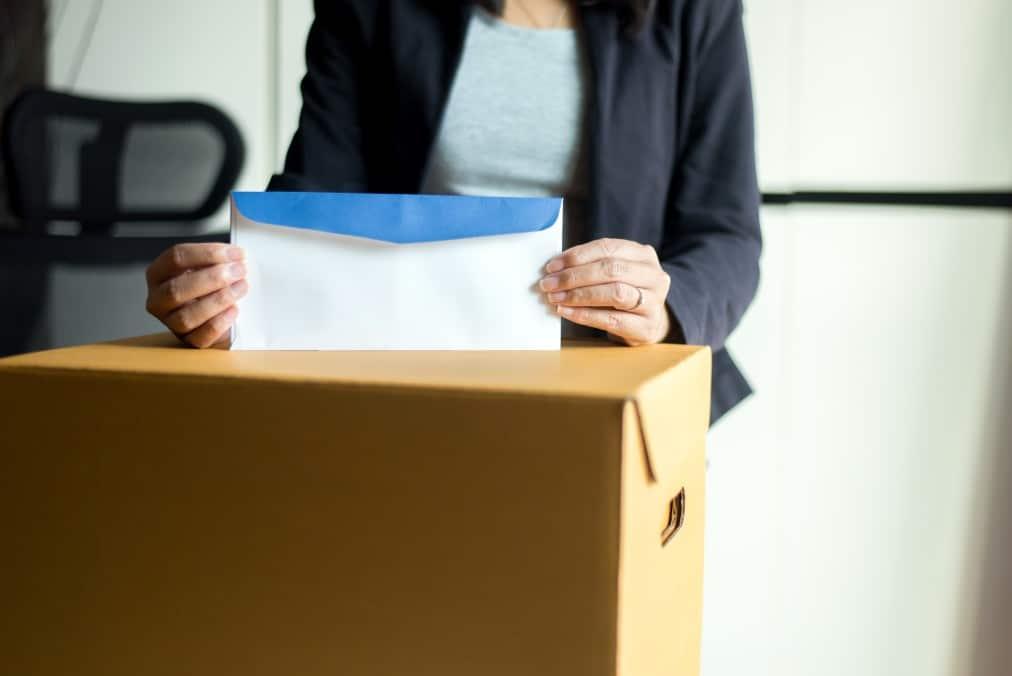 causas de rescisão indireta do contrato de trabalho - mulher segurando envelope sobre uma caixa