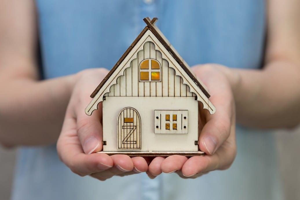 holding patrimonial - mulher segurando casa